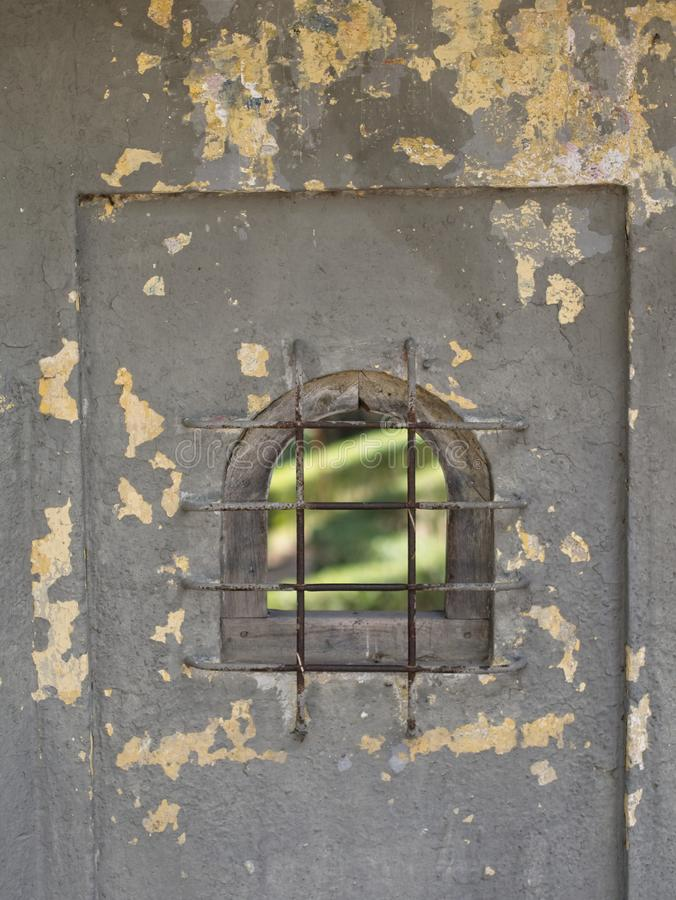 Weathered a peint le mur avec une petite fenêtre avec un trellis de fer image libre de droits