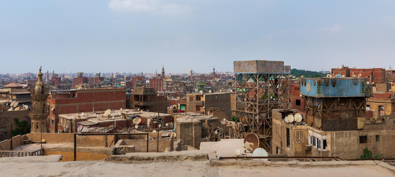 Weathered roofs of houses in old Cairo, Egypt. Shabby buildings with satellite dishes on rooftops located against blue sky in ancient city of Cairo, Egypt royalty free stock photo