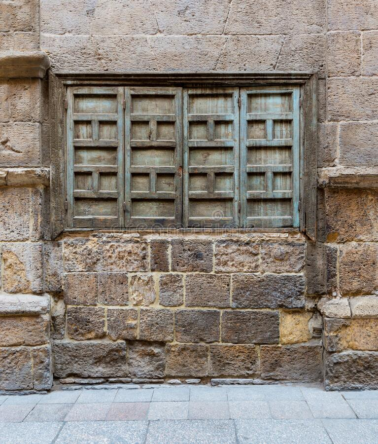 Weathered stone bricks wall and green grunge closed shuttered window on abandoned district royalty free stock photo