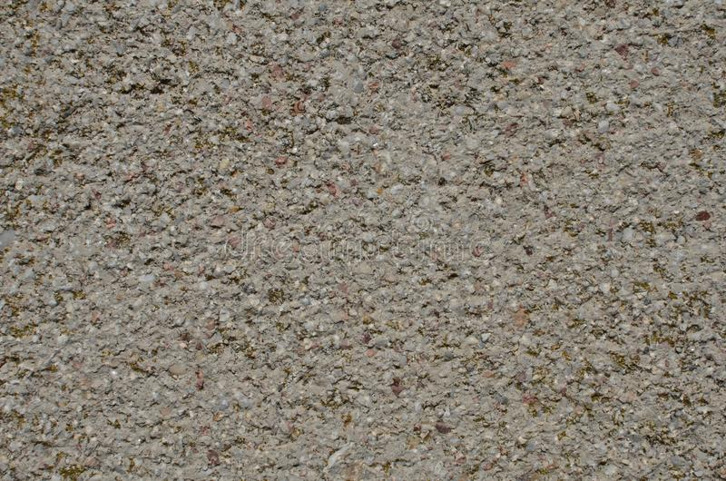 Aged textured surface of the artificial stone material. Weathered textured surface of an artificial stone made of mixture of mortar and tiny marble pieces of stock image
