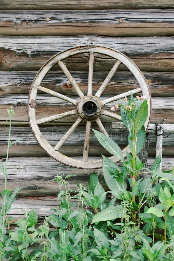 Weathered wall of old barn with wood coach wheel. royalty free stock photo