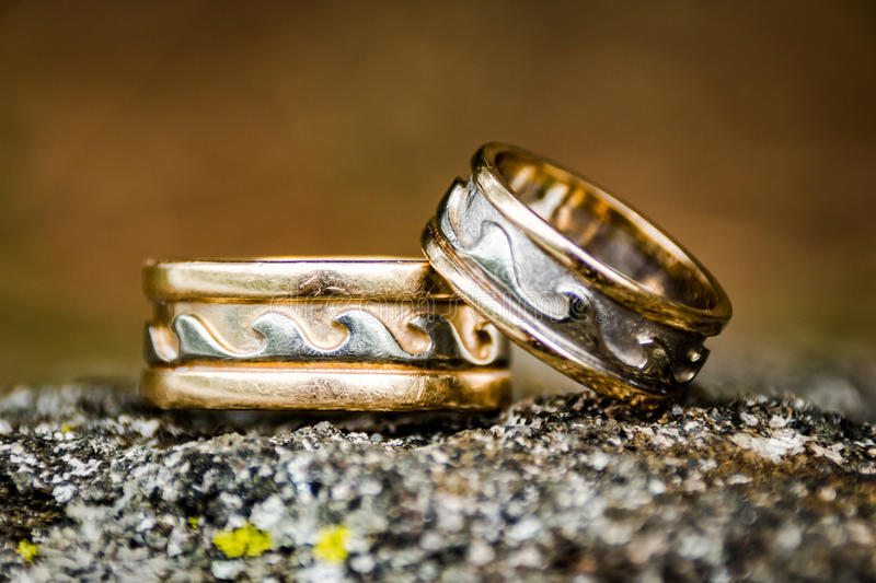 Weathered Wedding Rings. Close up of pair of worn and weathered wedding rings with a wave pattern royalty free stock images