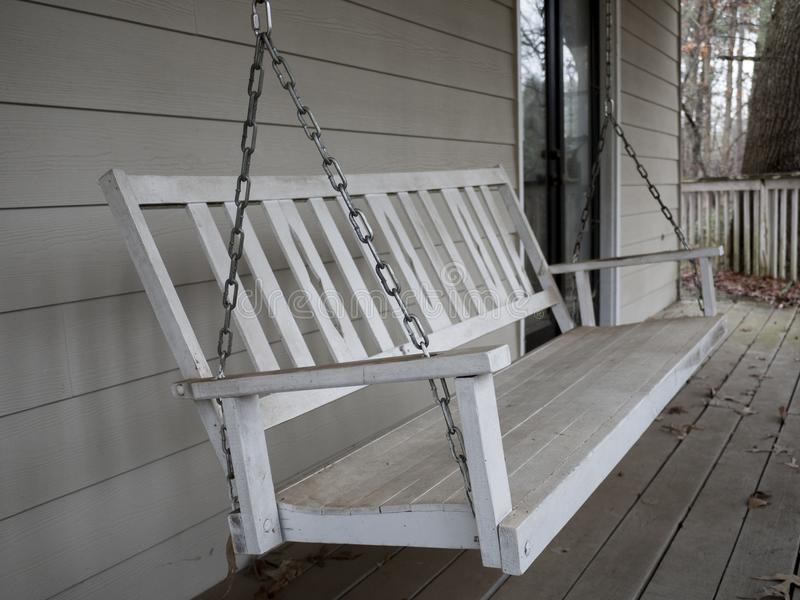 White Wooden Porch Swing. A weathered white wooden porch swing suspended with metal chains on an outside deck stock photos