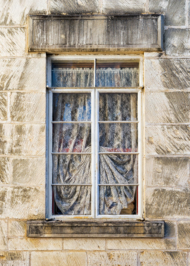 Weathered Window in a Limestone Wall. Old metal-framed, draped window set within a sturdy limestone wall on the front of an old sanitarium in Central Texas stock photos