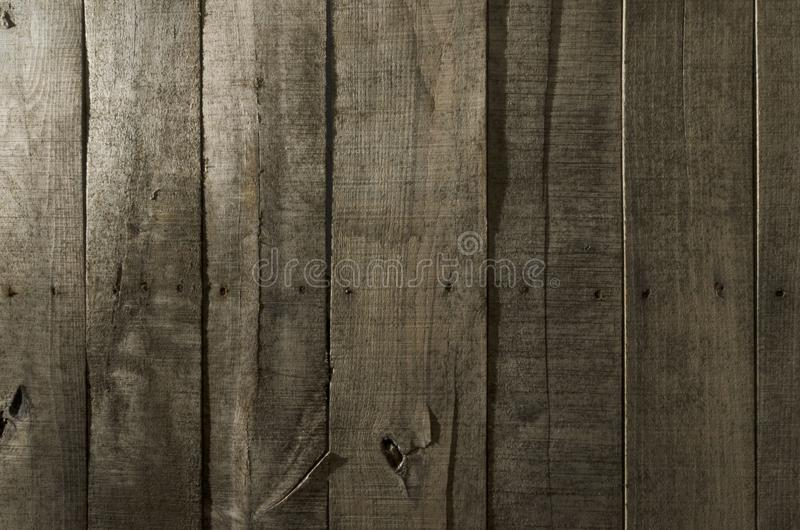 Weathered wood background. Aged wood slat wall in shadow illuminated from the top stock photo