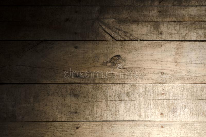 Weathered wood background. Aged wood slat wall in shadow illuminated from the right side royalty free stock photo