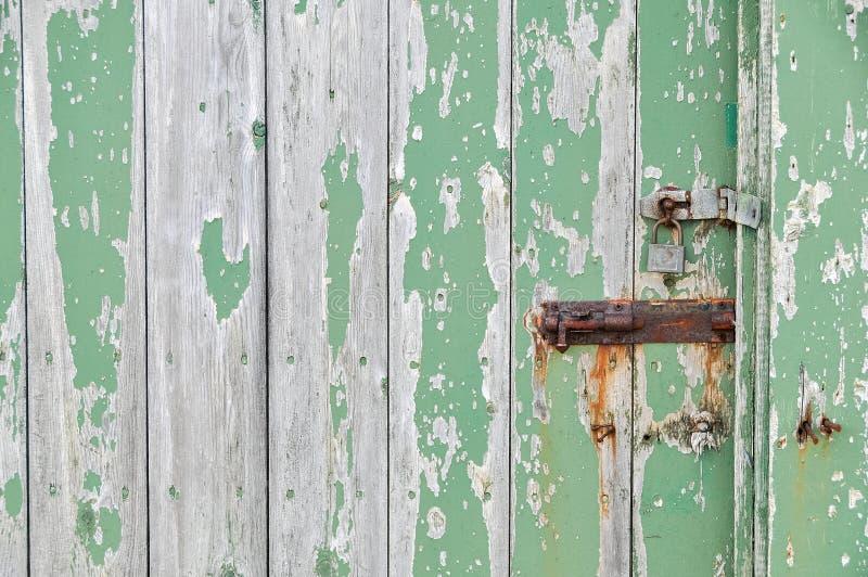 Weathered wooden door peeling green paint stock image