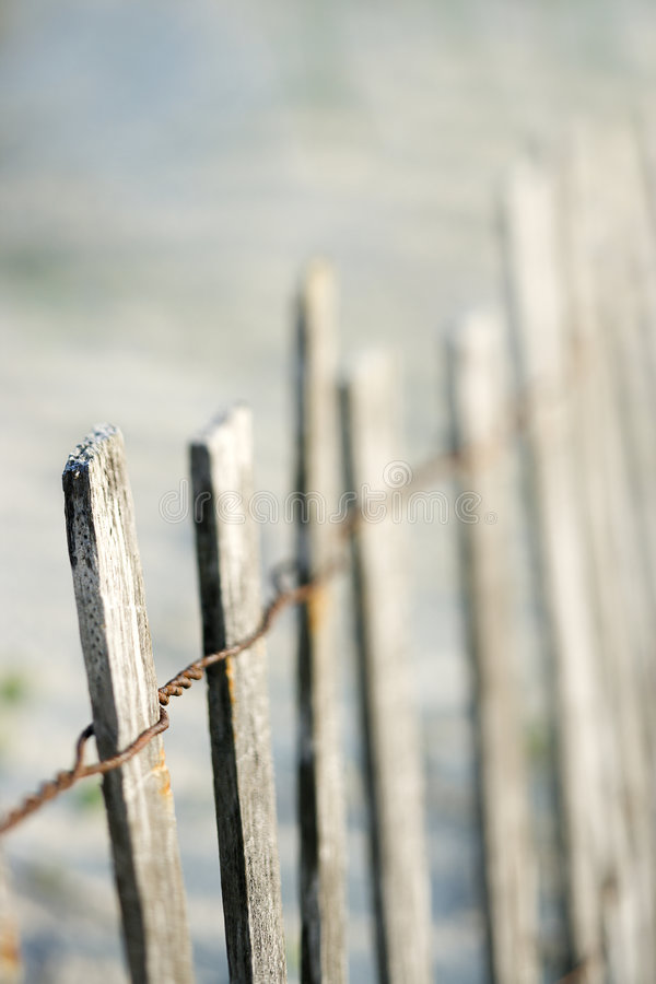 Weathered wooden fence on beach. stock photos