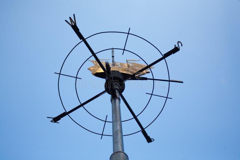 Weathervane bajo la forma de rosa de vientos con una figura de un sh foto de archivo