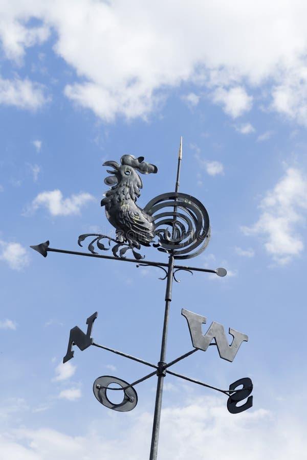 Weathervane de coq contre le ciel bleu et les nuages blancs image libre de droits