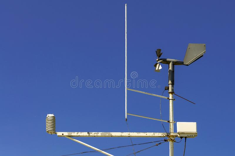 Weathervane weather station with a propeller and other measuring devices against a blue sky. royalty free stock photos