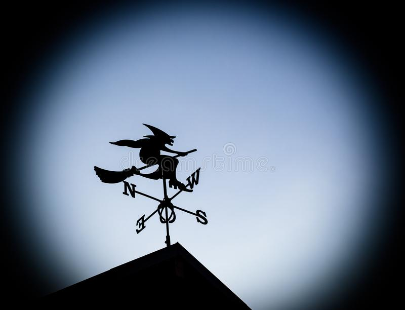 Weathervane witch on a broom. Weathervane old witch on a broom. Black silhouette weathervane on a rooftop, hag stock image