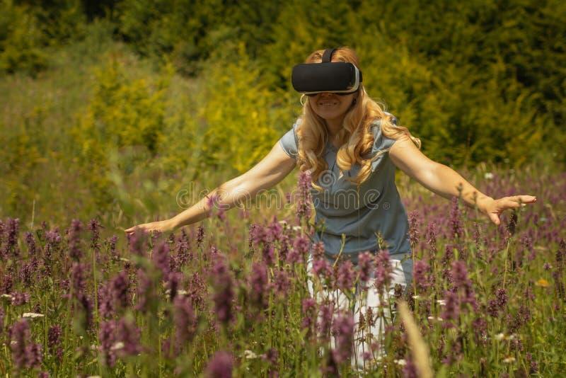 Weating virtuell verklighethörlurar med mikrofon för kvinna som sitter i mitt av ett fält av blommor Immersive VR erfarenhet arkivfoton