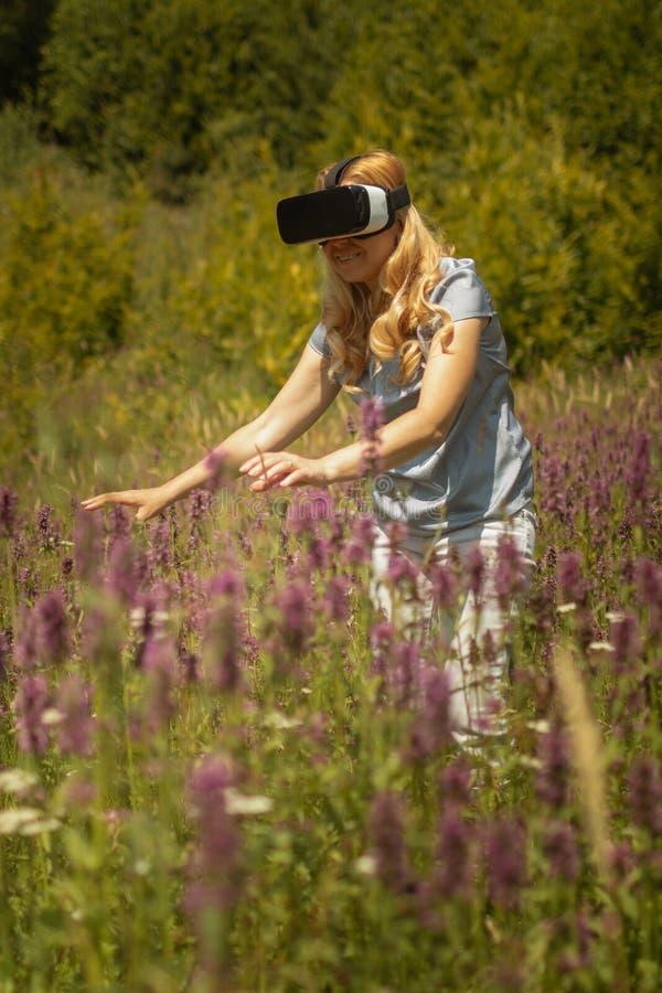 Weating virtuell verklighethörlurar med mikrofon för kvinna som sitter i mitt av ett fält av blommor Immersive VR erfarenhet royaltyfri foto