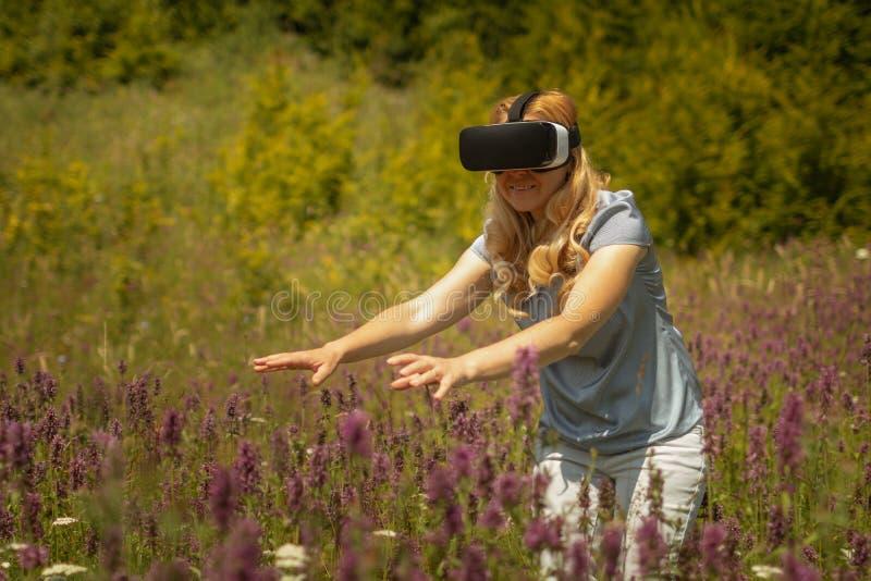 Weating virtuell verklighethörlurar med mikrofon för kvinna som sitter i mitt av ett fält av blommor Immersive VR erfarenhet royaltyfria bilder