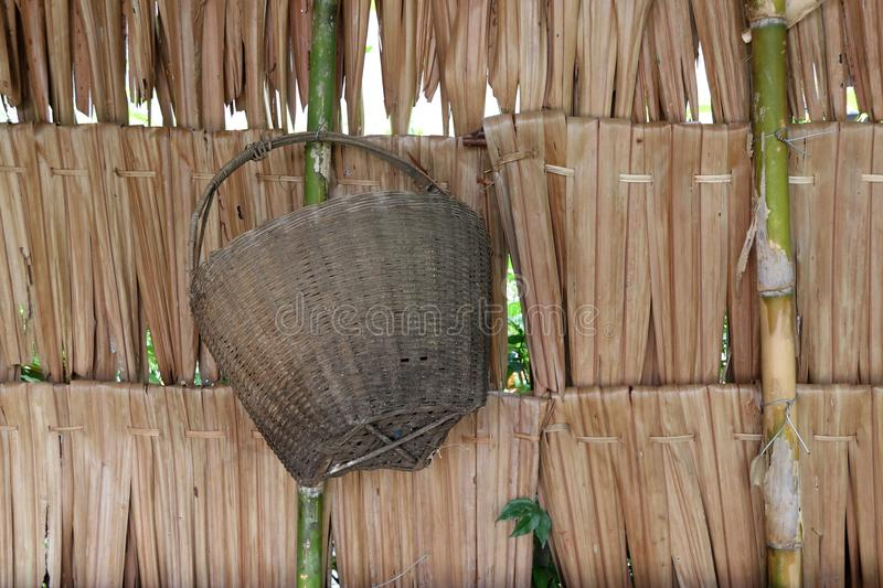 weave bamboo basket hanging on the thatch wall, it is a container of Thailand people days before. stock images