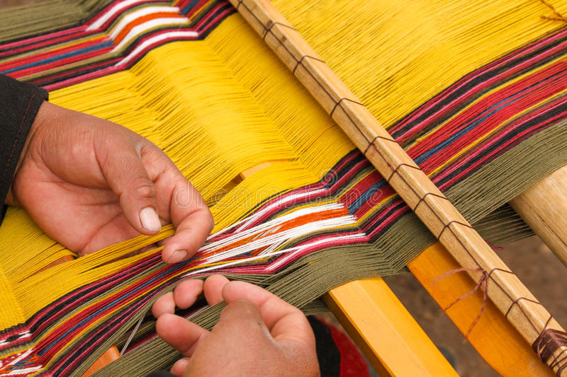 Weaving Naturally Dyed Wool. Up close of hands weaving colorful naturally dyed wool on a loom stock images