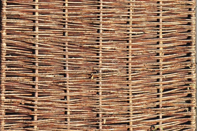Weaving from willow branches. Background for the design of natural components. Handwork. Use of natural resources. Fence from tree royalty free stock image