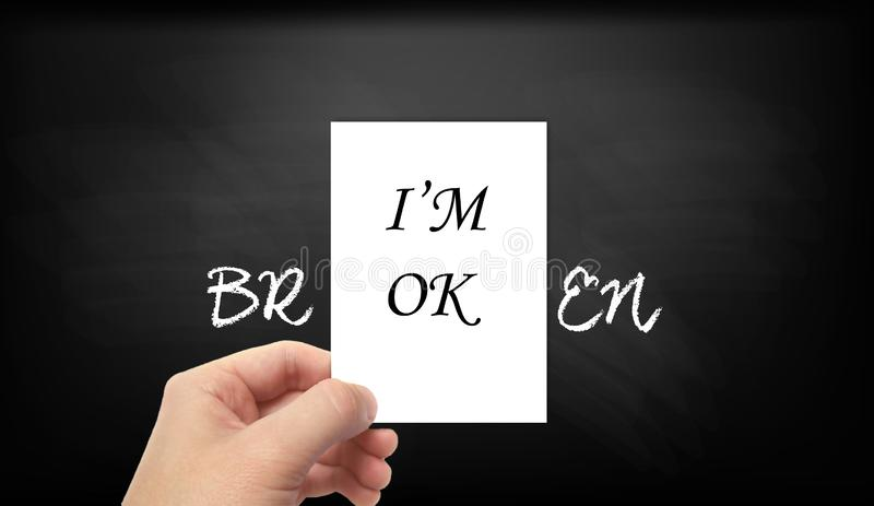 """""""I'M OK - BROKEN""""  Fake mask for hiding real emotions. Hand holding a piece of white paper in front of a blackboard background. `I`m ok` written royalty free stock image"""