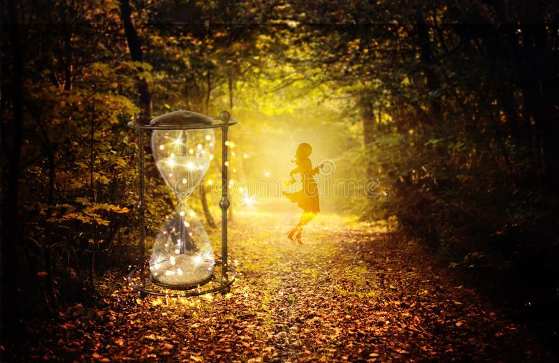 Magical hourglass and female guide in the enchanted forest. A magical hourglass in the forest with bright glowing lights and sparkles. Silhouette of a girl stock image