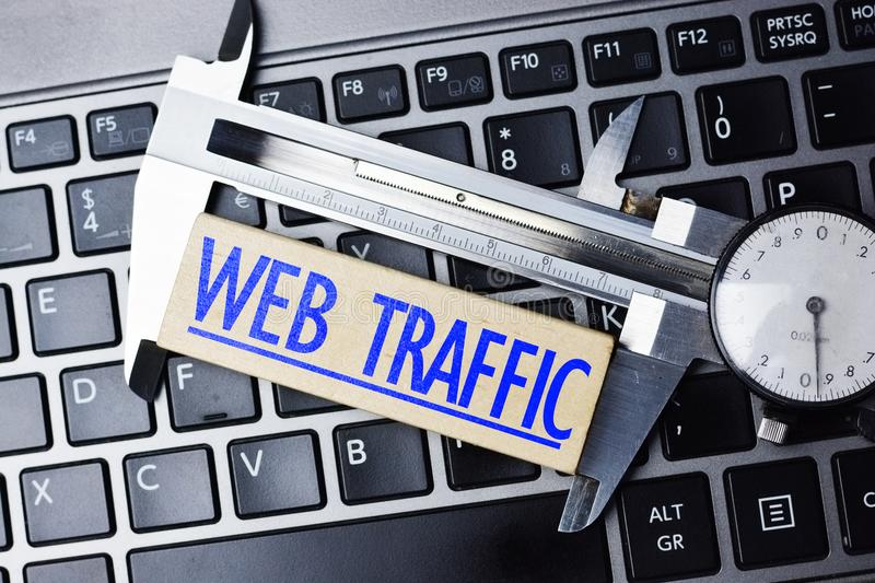 Web analytics concept, with caliper on laptop keyboard measuring online website traffic royalty free stock photo