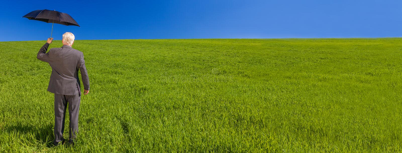 Web banner panoramic business concept photograph of a businessman standing in a green field under a bright blue sky holding and. Umbrella royalty free stock photo