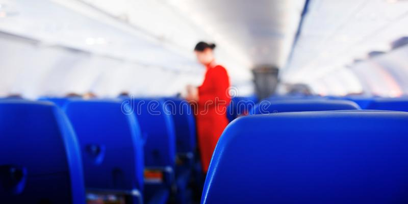 Web banner passenger seat in airplane, Interior of airplane and stewardess background. Stewardess renders services for passengers stock photography