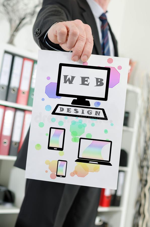 Web design concept shown by a businessman. Paper showing web design concept held by a businessman royalty free stock image