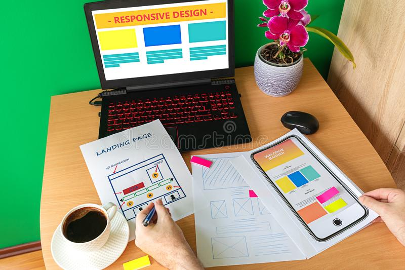 Web designer hand sketching responsive website for laptop and mobile phone stock images