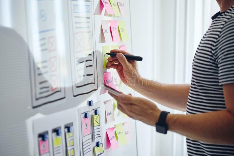Web designer planning website ux app development with marker pen. On whiteboard royalty free stock image