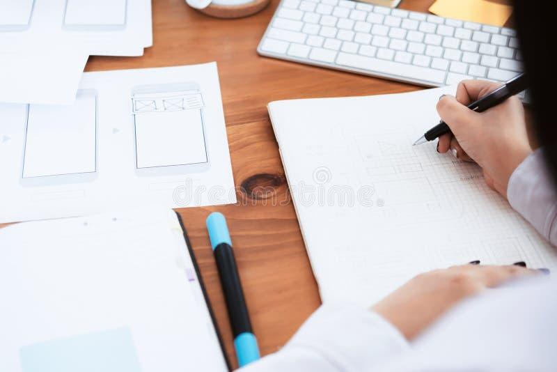 Web designer, UX UI designer designing mobile application user interface. Creative planning application development sketch layout wireframe design royalty free stock photos