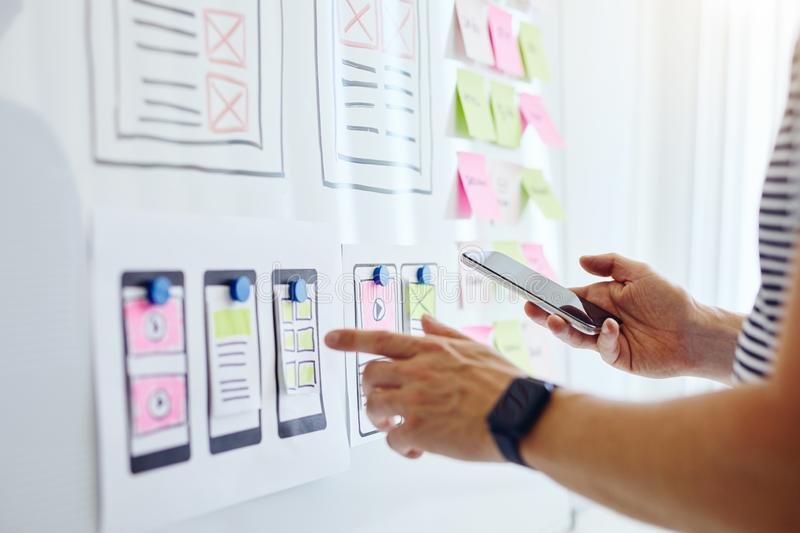 Web developer with mobile phone planning website ux app development. On white board stock photos