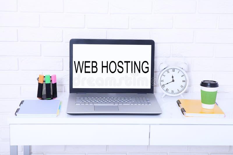 Web hosting Parola sul monitor Posto di lavoro con il computer e la tazza di caffè Derisione alta e spazio della copia fotografia stock libera da diritti