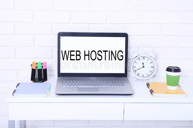 Web hosting. Word on monitor. Workplace with computer and cup of coffee. Mock up and copy space royalty free stock photo