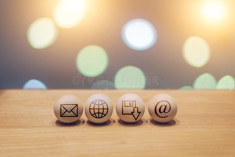 Web internet logo concept on wooden balls. Mail globe download at logos. Bokeh with light on background royalty free stock image