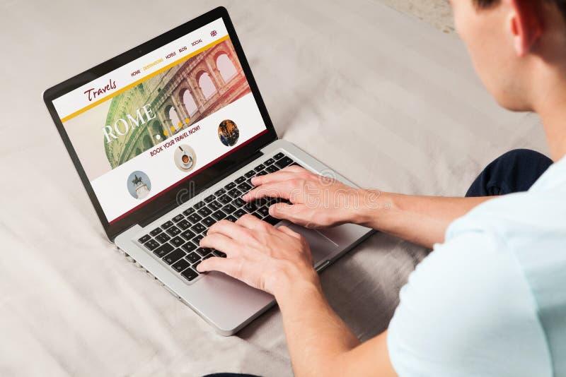 Web site de viagem em uma tela do portátil Homem que usa o para procurar o destino do curso foto de stock