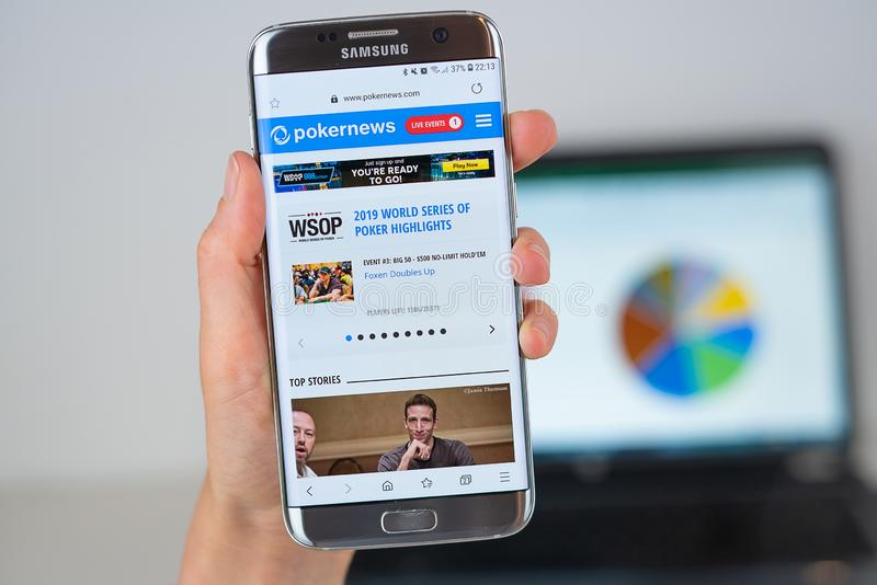 Web site of Pokernews company on phone screen stock image
