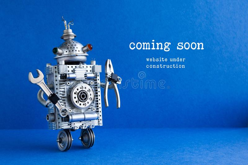 Web site under construction Coming Soon page. Toy robot with hand wrench and pliers. Blue background. Web site under construction Coming Soon page. Toy robot royalty free stock photography