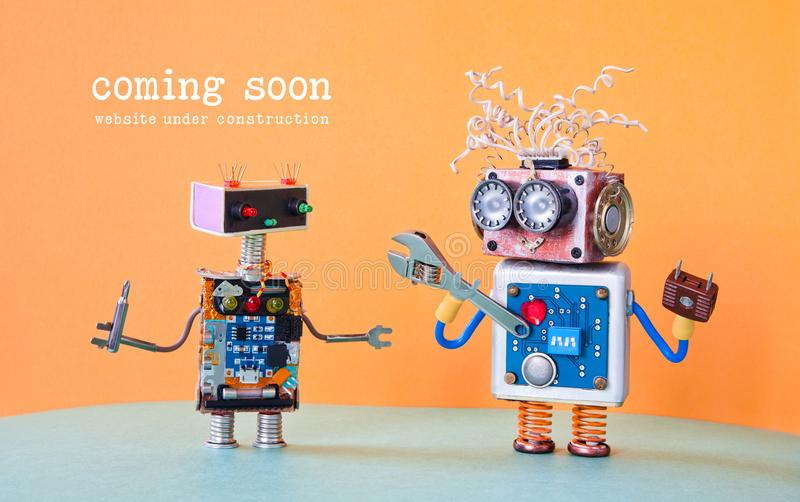 Web site under construction coming soon template page. Service robots maintenance with adjustable spanner screwdriver. Orange background stock photography