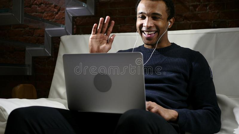 Web Videopraatje op Laptop door de Afrikaanse Mens bij Nacht, Hoofdtelefoons stock foto