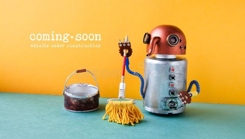 Webbplats under konstruktion som snart kommer mallsida Robotpackning med golvmopp och hinken av vatten, orange vägggräsplan royaltyfri fotografi