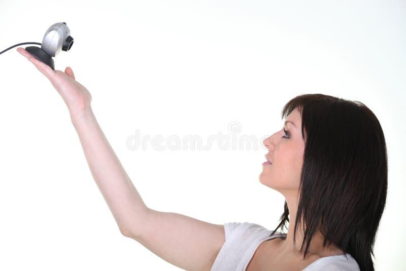 Webcam della holding della giovane donna su priorità bassa bianca immagine stock libera da diritti