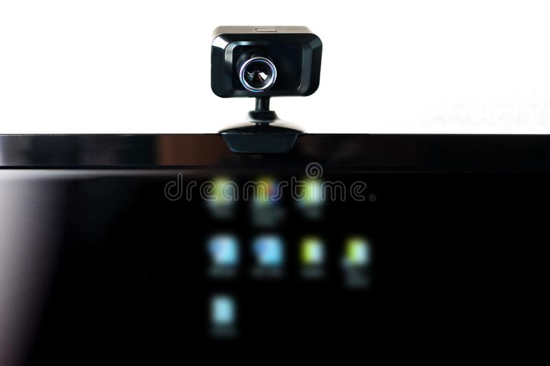Webcam di USB, macchina fotografica di web, montata sul monitor del computer con le icone vaghe sullo schermo nero E fotografia stock libera da diritti