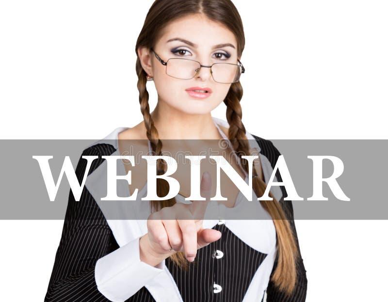 Webinar escrito en la pantalla virtual la secretaria atractiva en un traje de negocios con los vidrios, prensas abotona en las pa fotos de archivo libres de regalías