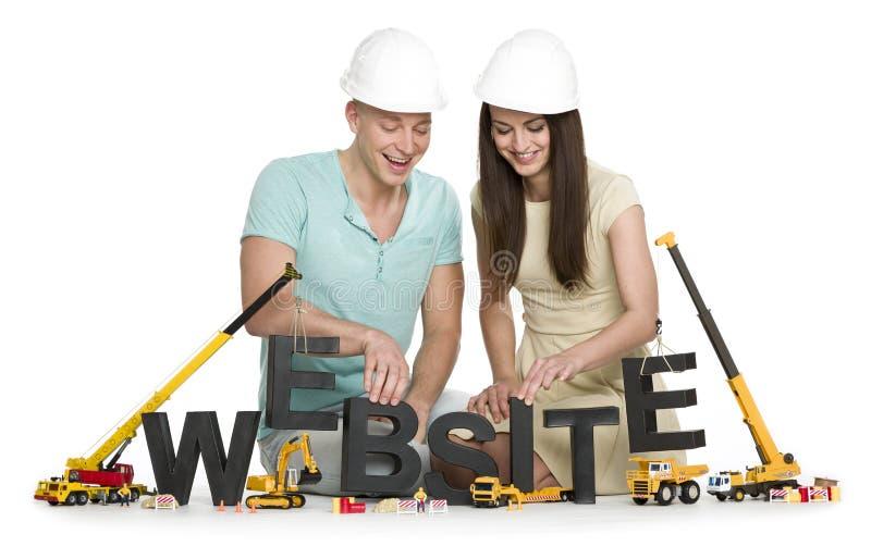Website in aanbouw: Blije man en vrouw die websit bouwen stock foto's