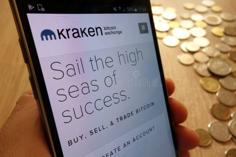 Website för Kraken cryptocurrencyutbyte som visas på smartphonen och bunt av mynt arkivbild