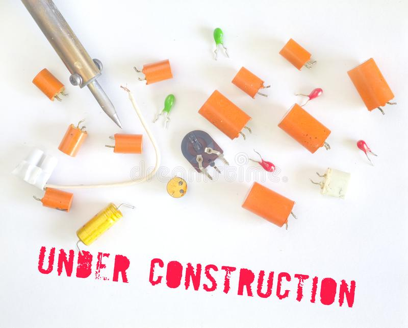 Website under construction sign with defective capacitors and soldering iron royalty free stock photos