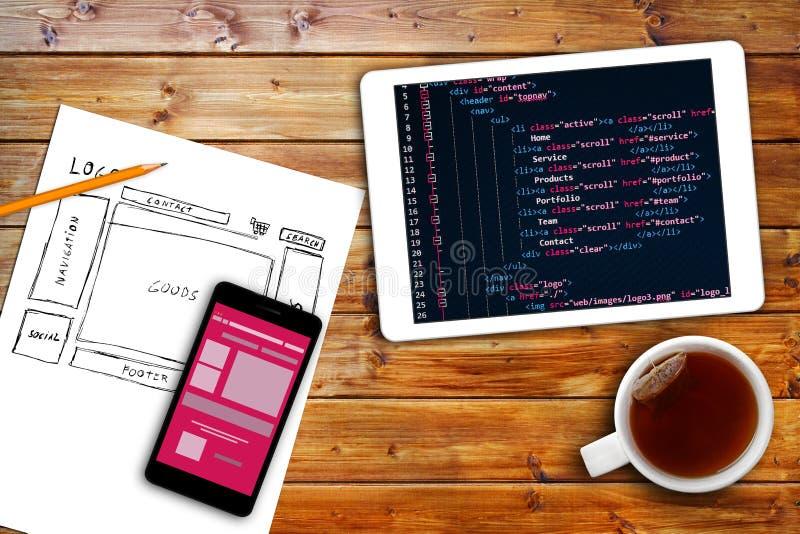 Website wireframe schets en programmeringscode inzake digitale tablet stock afbeelding
