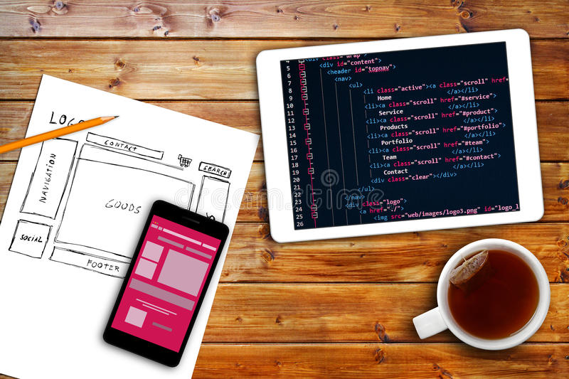 Website wireframe sketch and programming code on digital tablet stock image