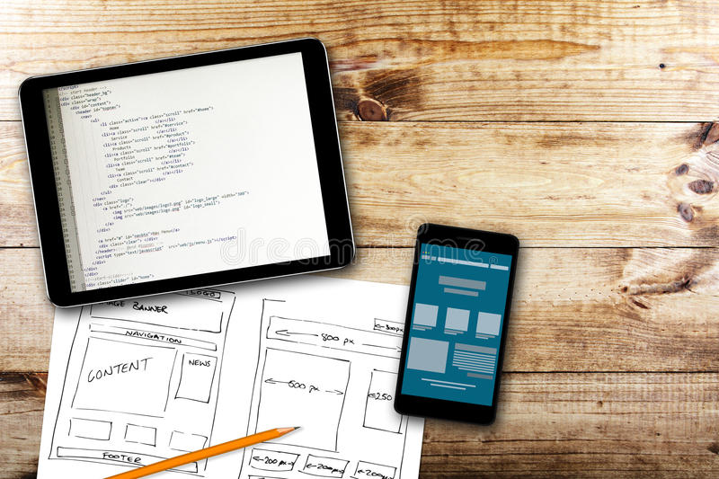Website wireframe sketch and programming code on digital tablet stock images